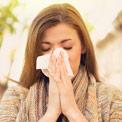 Brünette Frau schnäuzt mit geschlossenen Augen in ein Taschentuch