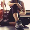 Junge Frau in dunkler Sportbekleidung sitzt im Fitnessstudio auf dem Boden mit Beinen überkreuzt