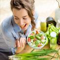 Junge Frau sitzt an einem Tisch mit der Gabel im Mund und hält eine Schüssel mit Salat in der anderen Hand