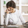 Junge Frau sitzt an Tisch und stützt ihren Kopf verzweifelt an der Hand ab