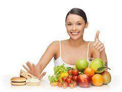 Frau sitzt vor einem Berg Obst und Gemüse und einem Berg Fast Food und schiebt das Fast Food mit einer Hand weg