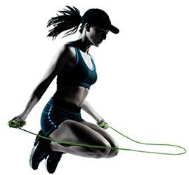 Frau in Sport-BH und Shorts springt Seil auf dunklem Hintergrund