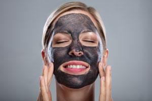 Frau trägt eine schwarze Gesichtsmaske, berührt ihre Wangen und lacht