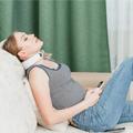 Frau liegt auf dem Sofa und trägt das U-neck Nackenmassagegerät