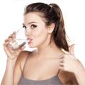 Brünette Frau mit Pferdeschwanz trinkt Wasser aus einem Glas