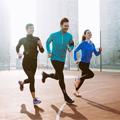 Zwei Frauen und ein Mann joggen nebeneinander und lachen