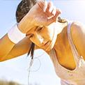 Frau beim Sport unter freiem Himmel wischt sich mit weißem Schweißband Schweiß von der Stirn