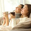 Zwei Frauen lehnen sich mit geschlossenen Augen zurück und halten Tassen in den Händen