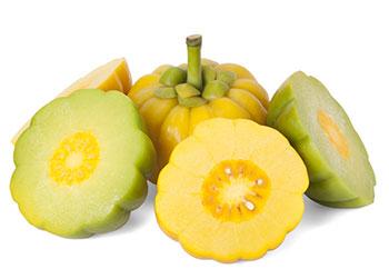 Eine ganze gelbe Garcinia Cambogia umgeben von aufgeschnittenen gelben und grünen Garcinia Früchten auf weißem Hintergrund