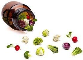 Aus einer braunen Glasflasche fällt verschiedenes Gemüse