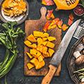 Holzbrett mit geschnittenem orangen Kürbis und Messer darauf umgeben von Lebensmittel