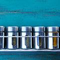 Silberne kleine Dosen für Gewürze auf Regal vor türkisem Hintergrund