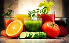 Fünf Gläser mit bunten Obst- und Gemüsesäften und Obst und Gemüse davor auf einem Tisch