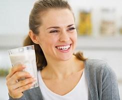 Frau lacht und hält ein großes Glas mit einer milchigen Flüssigkeit in der Hand