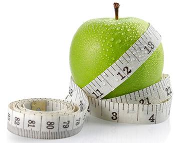 Grüner Apfel der mit einem weißen Maßband umwickelt ist auf weißem Hintergrund