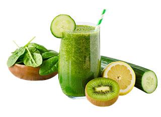 Grüner Smoothie in einem Glas neben einer Zitrone, einer Gurke, Spinat und einer Kiwi