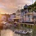 Häuserlandschaft an einem Fluss mit Booten bei Sonnenaufgang