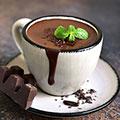 Weiße Keramiktasse gefüllt mit heißer Schokolade auf braunem Hintergrund