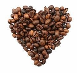 Ein kleines aus gerösteten Kaffeebohnen geformtes Herz auf weißem Hintergrund