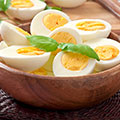 Eine Holzschüssel mit gekochten halb-aufgeschnittenen Eiern