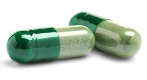 Zwei Kapseln mit grüner Füllung auf weißem Hintergrund