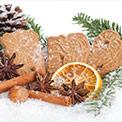 Zwei Kekse, Zimtstangen und Tannenzweige mit Schneeflocken