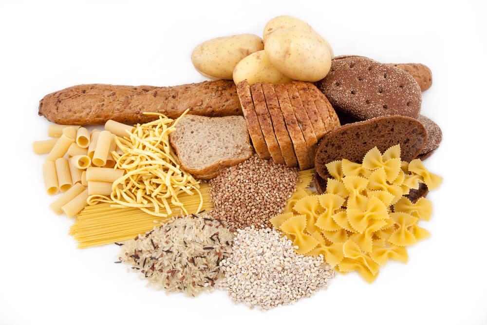 Brot, Kartoffeln, Nudeln und Getreide liegen nebeneinander auf weißem Hintergrund