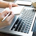 Laptop Tastatur und zwei Hände die einen kleinen Block und einen Stift halten