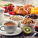 Leckeres Frühstück mit Müsli, Kaffee, Obst und Gebäck auf hölzernem Untergrund