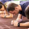 Männer und Frauen in violetten Shirts die gleichzeitig die Plank Position halten