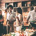 Frauen und Männer auf einer Party stehen vor dem Buffet mit kleinen Happen