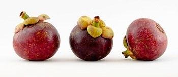 Drei Mangostan Früchte nebeneinander auf weißem Hintergrund
