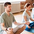 Mann und Frau in Yogastudio die in der Schneidersitzposition verweilen