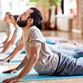 Mann auf blauer Yogamatte während er die Sanfte Kobra Yoga Position ausübt