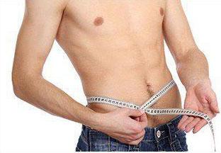 Oberkörperfreier Mann misst seinen Bauchumfang mit einem weißen Maßband