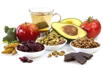 Drei Schüsseln mit Nüssen und getrockenten Früchten umgeben von Obst, Gemüse und einem Teeglas