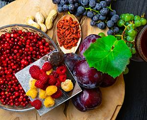 Himbeeren, Pflaumen, Goji, Cranberries und Trauben auf einem Tisch
