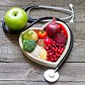 Obst und Gemüse in einer herzförmigen Schale, daneben liegen ein Apfel und ein Stethoskop