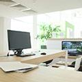 Helles offenes Büro mit Holztischen und Computerbildschirmen