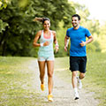 Ein Mann und eine Frau joggen auf einem Feldweg, im Hintergrund ist ein Wald zu sehen