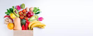 Eine Papiertüte, aus der verschiedenes Obst und Gemüse herausfällt