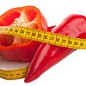 Ein roter halb-aufgeschnittener Paprika und ein roter länglicher Paprika mit einem Maßband umwickelt auf weißem Hintergrund