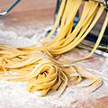 Selbst gemachte Pasta die gerade aus dem Gerät kommt und auf Mehl liegt