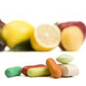 Verschiedenfarbige Pillen im Vordergrund und Zitronen verschwommen im Hintergrund
