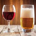 Ein Rotweinglas mit Rotwein gefüllt und ein Bierglas mit Bier gefüllt auf hölzernem Hintergrund