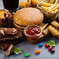 Süßigkeiten und Fast Food nebeneinander auf dunklem Untergrund