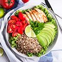 Weiße Schüssel mit Avocado, Hühnerfleisch, Quinoa, Tomaten und Salat auf einem weiß-blauen Geschirrtuch