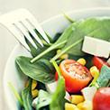 Schüssel mit grünem Salat und Tomaten in weißer Schüssel mit Gabel