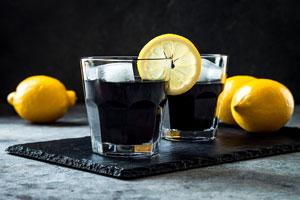 Zwei gläser mit schwarzen Getränken, einer Zitronenscheibe und ganzen Zitronen
