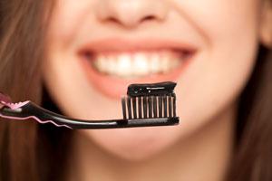 Schwarze Zahncreme auf einer Zahnbürste mit einer lächelnden Frau im Hintergrund